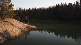 La mujer joven toma la foto usando su app del tel?fono de un lago del color de la turquesa en los Estados b?lticos en Letonia almacen de video