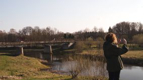 La mujer joven toma la foto usando su app del tel?fono del r?o con un puente en el fondo en la ciudad Sabile de los Estados b?lti almacen de metraje de vídeo