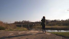 La mujer joven toma la foto usando su app del tel?fono del r?o con un puente en el fondo en la ciudad Sabile de los Estados b?lti almacen de video