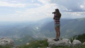 La mujer joven toma imágenes de la alta montaña metrajes