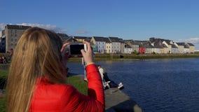 La mujer joven toma las fotos de las casas coloridas en Galway Claddagh - GALWAY, IRLANDA - 11 DE MAYO DE 2019 almacen de video
