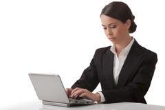 La mujer joven trabaja en el ordenador fotografía de archivo