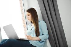 La mujer joven trabaja en el ordenador portátil y se sienta en el alféizar Fotografía de archivo libre de regalías