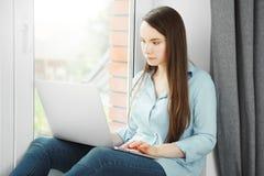 La mujer joven trabaja en el ordenador portátil y se sienta en el alféizar Imagenes de archivo
