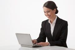 La mujer joven trabaja en un ordenador imagen de archivo