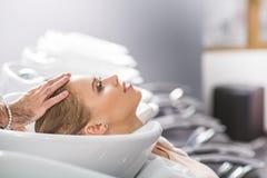 La mujer joven tranquila se está sentando en los peluqueros Imagen de archivo