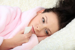 La mujer joven triste miente en un sofá y sostiene un tejido en una mano Fotografía de archivo