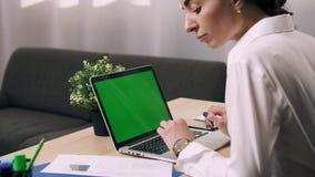 La mujer joven utiliza el ordenador en su lugar de trabajo en oficina