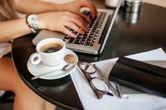 La mujer joven utiliza el ordenador portátil en café Fotografía de archivo