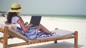 La mujer joven utiliza el ordenador portátil en la playa blanca cerca del océano metrajes