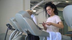 La mujer joven utiliza el teléfono que camina en la rueda de ardilla almacen de metraje de vídeo