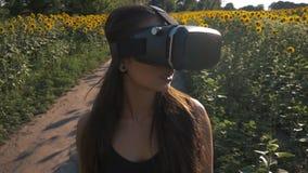 La mujer joven utiliza el visualizador en forma de visor al aire libre Jugar al juego usando el VR-casco para los teléfonos elega almacen de video