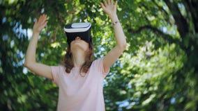 La mujer joven utiliza el visualizador en forma de visor en el parque Jugar al juego usando el VR-casco para los teléfonos elegan almacen de metraje de vídeo