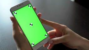 La mujer joven utiliza smartphone con greenscreen para la comunicación metrajes