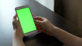 La mujer joven utiliza smartphone con greenscreen para la comunicación almacen de video
