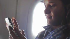 La mujer joven utiliza smartphone en el avión 1920x1080 metrajes
