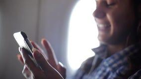 La mujer joven utiliza smartphone en el avión 1920x1080 almacen de metraje de vídeo