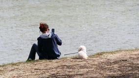 La mujer joven utiliza su smartphone en el río fotos de archivo libres de regalías