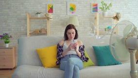 La mujer joven utiliza un smartphone que se sienta en el sofá delante de una fan eléctrica, escapes del calor almacen de video