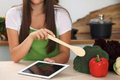 La mujer joven va a cocinar la comida sana de verduras Ciérrese para arriba del ama de casa con la cuchara de madera que señala e Fotografía de archivo