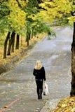 La mujer joven va con los bolsos Fotos de archivo libres de regalías
