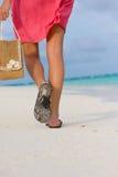 La mujer joven va para una caminata en una playa Foto de archivo libre de regalías