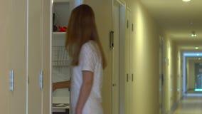 La mujer joven viene a su apartamento y abre una cerradura electrónica usando una llave electrónica metrajes