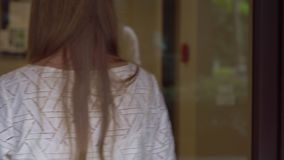 La mujer joven viene a su apartamento y abre una cerradura electrónica usando una llave electrónica almacen de metraje de vídeo