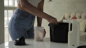 La mujer joven vierte el suero en la coctelera mientras que se coloca en cocina de la casa almacen de video
