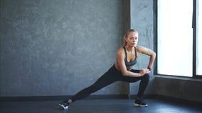 La mujer joven y atractiva que hace estirar de la pierna muscles en el gimnasio almacen de video