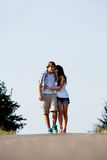 La mujer joven y el hombre está recorriendo en un camino en el verano al aire libre Foto de archivo