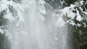 La mujer joven y el hombre lanza nieve para arriba metrajes