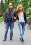 La mujer joven y el hombre que caminan en ciudad parquean Foto de archivo
