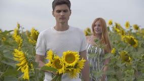 La mujer joven y el hombre que se divierten al aire libre El individuo que sostiene los girasoles en el primero plano mientras qu almacen de video