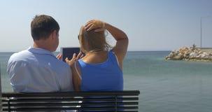 La mujer joven y el hombre se están sentando en banco en la playa en fondo del horizonte del mar que miran algo en tableta y almacen de metraje de vídeo