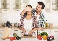 La mujer joven y el marido están cocinando con las verduras frescas El marido la cierra mano de los ojos imagenes de archivo