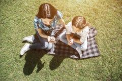 La mujer joven y el pequeño niño se están sentando juntos en la manta y están llevando a cabo el contra del helado La muchacha ha foto de archivo libre de regalías