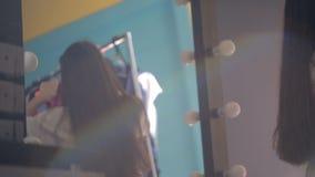 La mujer joven y hermosa se está colocando delante del espejo que elige el vestido metrajes
