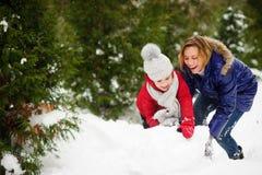 La mujer joven y la muchacha de la edad de escuela construyen un muñeco de nieve Fotos de archivo libres de regalías