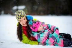 La mujer joven y la muchacha preciosas en chaquetas brillantes mienten en nieve Foto de archivo