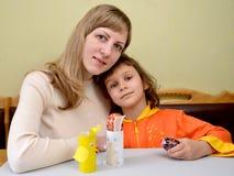 La mujer joven y la pequeña hija con los huevos de Pascua hecho a sí mismos del supportsfor Imagen de archivo libre de regalías