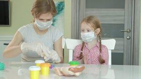 La mujer joven y la muchacha en máscaras médicas, mujer pone guantes en sus manos, juegos en el dentista, la madre y a la hija almacen de metraje de vídeo