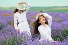 La mujer joven y la muchacha están en el campo de la lavanda, paisaje hermoso del verano con las flores rojas de la amapola Fotografía de archivo