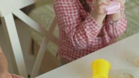 La mujer joven y la muchacha moldean sus dientes del plasticine, del juego en el dentista, de la madre y de la hija, manos del pr metrajes