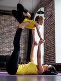 La mujer joven y la niña que hacen el vuelo de la yoga del socio plantean el ejercicio juntas fotografía de archivo libre de regalías