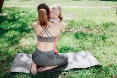 La mujer joven y su hija se están abrazando Ambos ellos se están sentando en carimate en hierba verde Hay un fichero de Imágenes de archivo libres de regalías