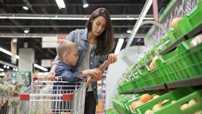 La mujer joven y su hijo están eligiendo la fruta en tienda, están tomando la fruta de las cajas plásticas y después las están ol almacen de video