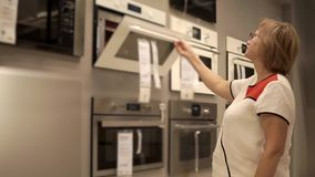 La mujer jubilada está mirando en los hornos en tienda al por menor, puertas de abertura almacen de video
