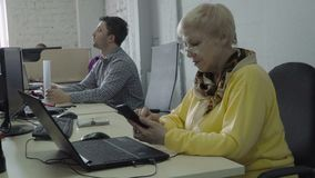 La mujer jubilada utiliza su teléfono en oficina durante el trabajo metrajes