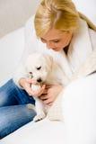 La mujer juega con el perrito blanco en el sofá Imagen de archivo libre de regalías